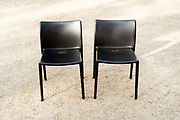 two chairs standing outside on dried-up grass