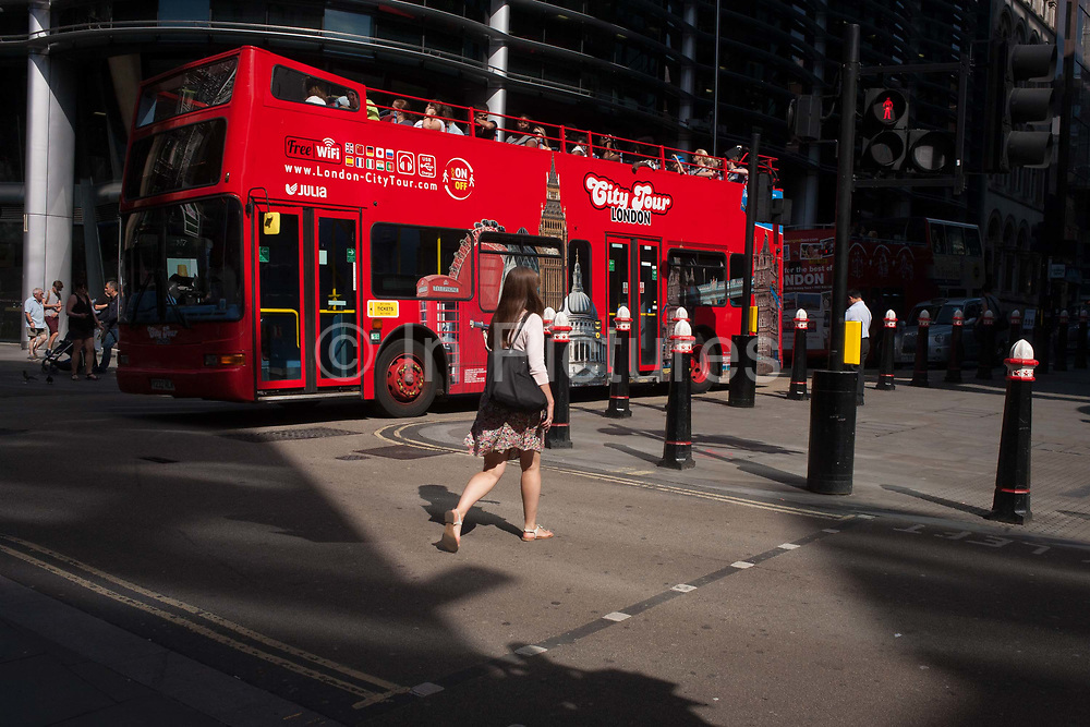 Tourists sit on the open top deck of a tour bus run by City Tour London as it makes it way along Cannon Street, on 24th August 2016, in the City of London, UK. Its route takes it along this busy road running across the capitals financial district, founded by the Romans in the first Century.