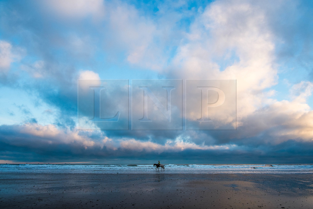 © Licensed to London News Pictures. 10/03/2014<br /> <br /> Saltburn, Cleveland, United Kingdom<br /> <br /> A rider exercises his horse along the beach at first light in Saltburn by the Sea in Cleveland.<br /> <br /> Photo credit : Ian Forsyth/LNP