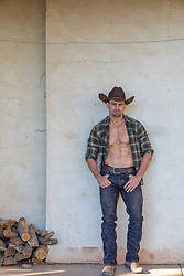 hot muscular cowboy with open shirt leaning against a wall