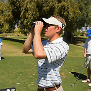 Golden State Golf Tour player Jason Cook measures the yardage as playing partners decide on club use.
