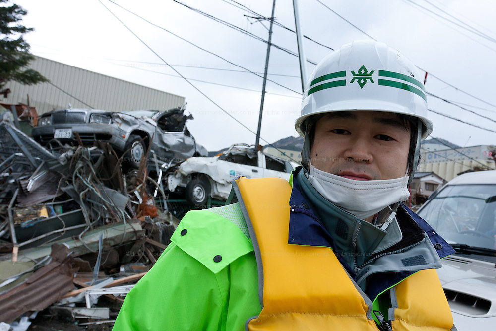 Osamu Onodera, a government official with the Iwate district, assists with clean up and rescue efforts after the tsunami that struck the north east coast of Japan on March 11th. Kamaishi, Iwate, Japan. March 17th 2011