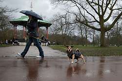 © Licensed to London News Pictures. 18/02/2021. London, UK. A woman shelters under an umbrella as she walks her dog during a rain shower in Greenwich Park. Flood warnings are in place in parts of the UK. Photo credit: George Cracknell Wright/LNP