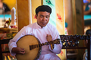 "29 MARCH 2012 - TAY NINH, VIETNAM:  A musician leads performs during noon prayers at the Cao Dai Holy See in Tay Ninh, Vietnam. Cao Dai (also Caodaiism) is a syncretistic, monotheistic religion, officially established in the city of Tây Ninh, southern Vietnam in 1926. Cao means ""high"" and ""Dai"" means ""dais"" (as in a platform or altar raised above the surrounding level to give prominence to the person on it). Estimates of Cao Dai adherents in Vietnam vary, but most sources give two to three million, but there may be up to six million. An additional 30,000 Vietnamese exiles, in the United States, Europe, and Australia are Cao Dai followers. During the Vietnam's wars from 1945-1975, members of Cao Dai were active in political and military struggles, both against French colonial forces and Prime Minister Ngo Dinh Diem of South Vietnam. Their opposition to the communist forces until 1975 was a factor in their repression after the fall of Saigon in 1975, when the incoming communist government proscribed the practice of Cao Dai. In 1997, the Cao Dai was granted legal recognition. Cao Dai's pantheon of saints includes such diverse figures as the Buddha, Confucius, Jesus Christ, Muhammad, Pericles, Julius Caesar, Joan of Arc, Victor Hugo, and the Chinese revolutionary leader Sun Yat-sen. These are honored at Cao Dai temples, along with ancestors.      PHOTO BY JACK KURTZ"