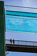 """London, United Kingdom, Jun 3, 2021: People are seen observing a 25-metre sky pool in Embassy Gardens linking two residential buildings in London's Nine Elms, floating 10 storeys above ground. The Sky Pool, described as """"the world's first floating pool"""", is only open to some of the development's residents, where rent is from about £1,800 to £6,500 per month. (Photo by Vudi Xhymshiti)"""