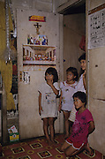 1989: Inside Kelabit native longhouse. Children near doorway with Christian religious and save the rainforest material. Long Napir, Limbang district, Sarawak, Borneo<br /> <br /> Tropical rainforest and one of the world's richest, oldest eco-systems, flora and fauna, under threat from development, logging and deforestation. Home to indigenous Dayak native tribal peoples, farming by slash and burn cultivation, fishing and hunting wild boar. Home to the Penan, traditional nomadic hunter-gatherers, of whom only one thousand survive, eating roots, and hunting wild animals with blowpipes. Animists, Christians, they still practice traditional medicine from herbs and plants. Native people have mounted protests and blockades against logging concessions, many have been arrested and imprisoned.