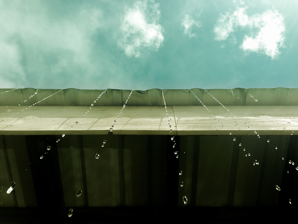 Melting snow dripping off metal roof