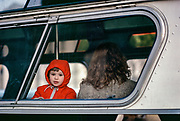 Child in Red Hood in Bus Window, New York City, New York, USA, December 1982