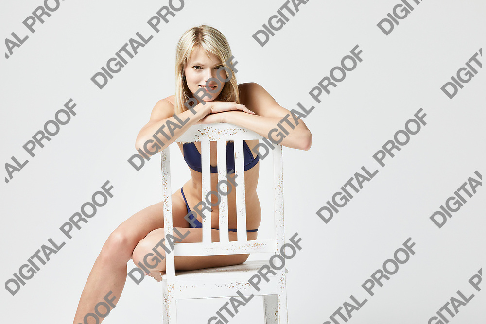 Reliable and confident woman seated and smiling while seated in a studio with a white background
