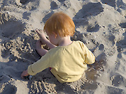 little child playing by herself in beach sand