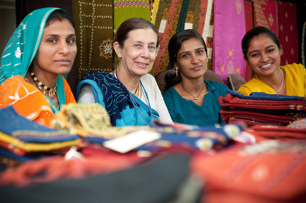 Judy Frater is an American anthropologist who has started a design school to teach villagers in Gujarat how to make traditional textiles. Here she is at the  Kala Raksha craft sale in Dehli selling her wares with some of the artisans she's trained.  (www.kala-raksha.org). New Delhi, October 2009<br /> <br /> From left: Chandrika Ben from Village Sumrasar, Judy Frater, Devi Ben from village Tundavandh, and Varsha ben form village Sumarsam. All villages are in the Kutch district of Gujarat.