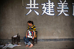 """Yang Zong Chun, 30, holding a picture of her daughter Shi Xue, 10, is seen  at Fuxin No.2 Primary  School in Wufu, Sichuan province.   """"I just want people to know about what happened here."""