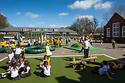 Children enjoying their playtime outdoors in the playground of South Farnborough Infant School, Hampshire, UK.   A group of young girls sit down to play a game, whilst many other children are running around and playing games in the sunshine.