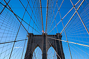 Piers and wire supports of Brooklyn Bridge and Stars and Stripes American flag, New York City