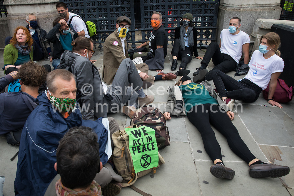 Climate activists from Extinction Rebellion, some of whom glued to the pavement, blockade the Houses of Parliament on 3 September 2020 in London, United Kingdom. Extinction Rebellion activists are attending a series of September Rebellion protests around the UK to call on politicians to back the Climate and Ecological Emergency Bill (CEE Bill) which requires, among other measures, a serious plan to deal with the UK's share of emissions and to halt critical rises in global temperatures and for ordinary people to be involved in future environmental planning by means of a Citizens' Assembly.