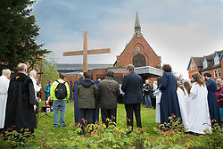 © Licensed to London News Pictures. 14/4/2016. Solihull, West Midlands, UK.  Easter Walk of Witness taking place in Solihull. Pictured, prayers and hymns outside St Augustine's Church. All the churches of Solihull coming together. Starting at St Augustine's Church around two hundred people walked behind a wooden cross into Mell Square for readings and prayers before continuing the walk to St Alphege Church.  Photo credit: Dave Warren/LNP