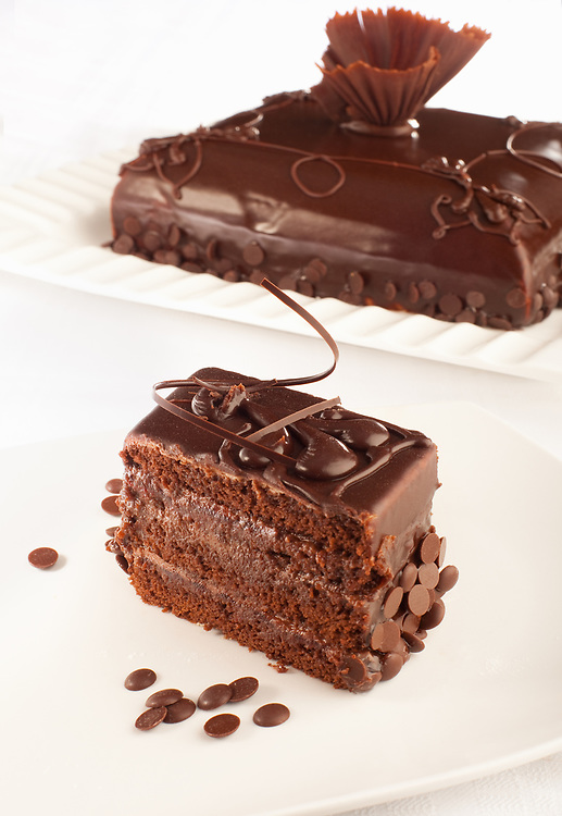 A styled Chocolate cake and a piece of that cake in front of it.