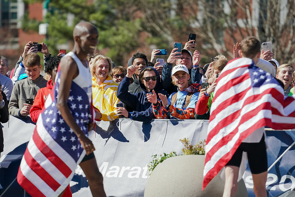 Fans cheer as Abdi Abdirahman (left) and Galen Rupp celebrate after coming in third and first, respectively, in the 2020 U.S. Olympic marathon trials in Atlanta on Saturday, Feb. 20, 2020. Photo by Kevin D. Liles for The New York Times