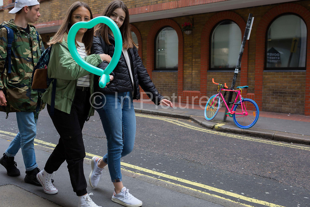 Two girls carrying a green heart-shaped balloon walk past a multi-coloured bike is locked to a post in a sidestreet in Londons West End, on 29th April 2019, in London, England.