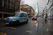 People and traffic pass as the Shard towers over Southwark Street on a wet day on 27th November 2019 in London, England, United Kingdom. The Shard, also referred to as the Shard of Glass, Shard London Bridge and formerly London Bridge Tower, is an 87-storey skyscraper in London that forms part of the London Bridge Quarter development.