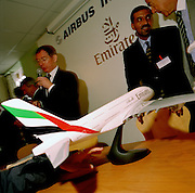 Emirates airlines announce the purchase of the very first Airbus A380 during the bi-annual aerospace industry expo at the Farnborough airshow in southern England. Executives congratulate themselves and speak into a micophone for the benefit of the press conference in the Emirates chalet at this important aviation and aerospace exposition. A scaled model of this new-generation of composite material aircraft sits on a table pointing to officials excited at their new business deal.