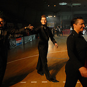 "Hungarian World Champion same-sex ballroom dancers Robert Tristan Szelei, left, and Gergely Darabos, second from left, wave to the crowd as they are introduced with other dancers at the start of the 2nd annual World Championship Same-Sex Ballroom Dancing competition in Budapest, Hungary, on October 21, 2006. ..Szelei and Darabos, who are known as the ""Black Swans,"" are the reigning world champions in men?s Latin same-sex ballroom dancing. They have been training and preparing to host the 2nd annual World Championship and the Csardas Cup, the first-ever Eastern European same-sex ballroom competition, both held at the Korcsarnok arena.  This is the pinnacle event of the blossoming same-sex ballroom scene...Szelei and Darabos went on to win the men?s Standard division and finished fourth in the Latin division. ..The event was organized by the US-based World Federation of Same-Sex Dancing, which hosted the first World Championship Same-Sex championships in 2005 in Sacramento, California. The Black Swans did a large amount of the coordination and planning in Budapest, a city that had never seen an event of this kind. When government funding fell through, they secured funding from patron Desire (accent on the ?e?) Dubounet, owner of the local Club Bohemian Alibi drag club. ..The World Championship events are newly recognized, but same-sex dancers have been competing on a national and international circuit for a number of years, especially in Europe, including at the Eurogames, the Gay Games, the London Pink Jukebox Trophy and the Berlin Open, among others. Countries including the United States, the Netherlands, Germany and, now, Hungary, hold their own national same-sex championships. Hungary held its first national championships in April 2006...Szelei and Darabos spent three months at the Sacramento Dancesport same-sex dance school in California this summer, on the first scholarship offered by the World Federation. The men both got their early training as opposite sex da"