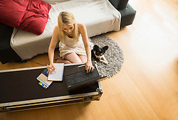 Beautiful young woman working on laptop with her dog in the living room, Munich, Bavaria, Germany