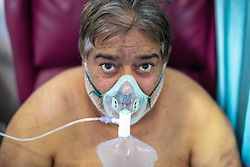 © Licensed to London News Pictures . 12/02/2021 .  Manchester , UK . Patient MAHMOOD AKHTAR (59) by his bed on a bay in Ward 4 , the Respiratory Cohort Area , where he is receiving oxygen therapy to aid his recovery from Coronavirus . Inside Manchester Royal Infirmary , where patients are being treated for the effects of Coronavirus . Photo credit : Joel Goodman/LNP