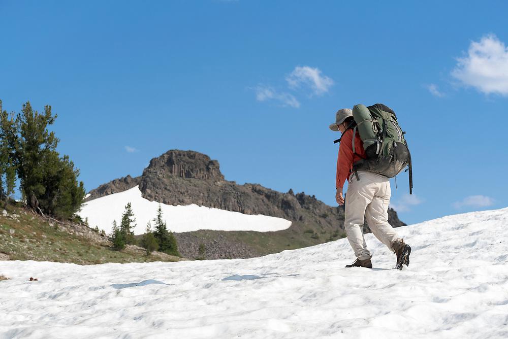 Backpacker hiking across a snowfield in Oregon's Wallowa Mountains.
