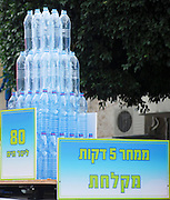 Save water display showing mineral water bottles containing 80 litres which is the amount of water used in a 5 minute shower