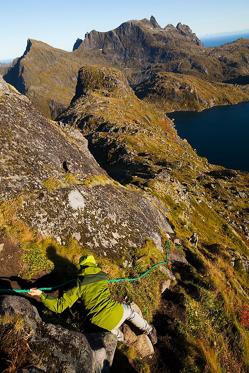 Liana Welty carefully descends a fixed rope installed on a steep section of the trail to Hermannsdalstinden on Moskenesoya, Lofoten Islands, Norway. Her husband Parmenter Welty waits patiently below.