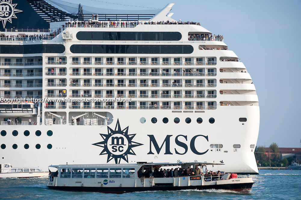 Large modern passenger cruise ship contrasts with Vaporetto waterbus sailing into Venice Italy