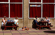 A sleeping Brit holidaymaker lies on the pavement outside the Exmoor Bar in the Butlins holiday camp at Minehead, Devon. A lady also sleeps with head propped up on an elbow with empty pint glasses on the bench. Butlins and other camp businesses went into decline when the masses preferred Spanish vacations but have since been revived as travel costs have again soared and holidays at home are once again popular.