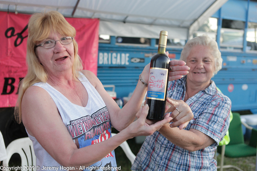 """The """"Sweet Bitches"""" a group of wives and significant others of Vietnam Veterans show a bottle of wine which bears their group name. Vietnam Veterans gather in Kokomo, Indiana for the 2009 reunion."""