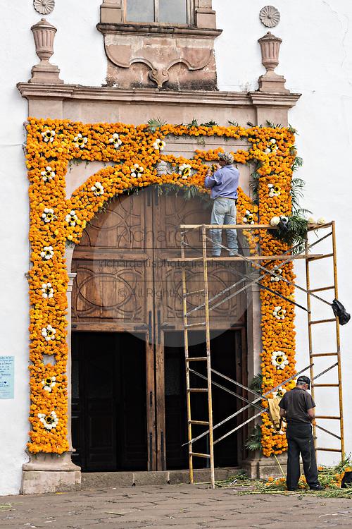 A Mexican man places marigolds on an ofrenda on the door to the Templo de Nuestra Señora del Sagrario church for the Day of the Dead festival in Santa Clara del Cobre, Michoacan, Mexico.