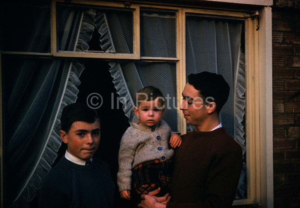 A portrait of three brothers of the same family have their picture taken outside their parents' home in Westcliff, England. The eldest is a teenager of approximately 17 and  is holding his youngest brother who is still only 12 months-old. The third boy is biting his lip while looking to the viewer, more anxiously than the other two. He is possibly 14 but both the elder lads wear identically-designed jumpers that cut across the throat to allow their clean white shirts and ties to remain visible. Apart from the young child, the elders share the same dark hair colour but genetically, they share one chromosome that has given them heavy eyebrows, a family trait. This was taken on Kodachrome film stock in the spring of 1961 so the look and feel of the image is dated with wonderfully muted colours that this Kodak film offered to consumers in the early 60s.