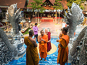 "03 APRIL 2016 - CHIANG MAI, THAILAND:  Buddhist monks walk into the ordination hall of Wat Sri Suphan. Wat Sri Suphan is also known as the ""Silver Temple"" because of its silver ubosot, or ordination hall. The temple is more than 500 years old but the silver ordination hall was recently remodeled. The ordination hall is covered in silver and the interior is completely done in silver and gold. It's traditionally served as the main temple for the silversmiths of Chiang Mai, whose community is around the temple.     PHOTO BY JACK KURTZ"