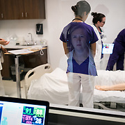 GREENVILLE, SC - OCTOBER 1: Nancy Allen is seen reflected in a one way mirror as as she controls a simulation patient for students of the Clemson University School of Nursing inside their high tech classrooms on the campus of Greenville Memorial Hopsital on October, 1 2018.  (Photo by Logan Cyrus/ The New York Times