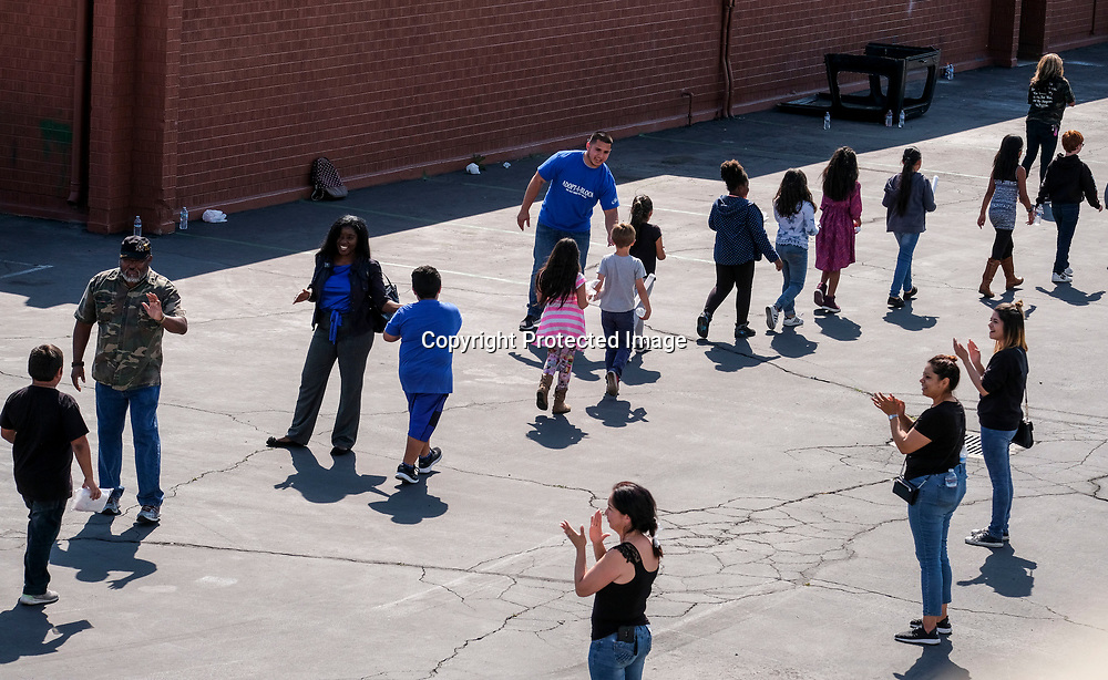 School staff greet students at North Park Elementary School, in relief at Cajon High School, Monday, April 10, 2017, in San Bernardino, Calif., after a deadly shooting occurred at the elementary school. (AP Photo/Ringo H.W. Chiu)