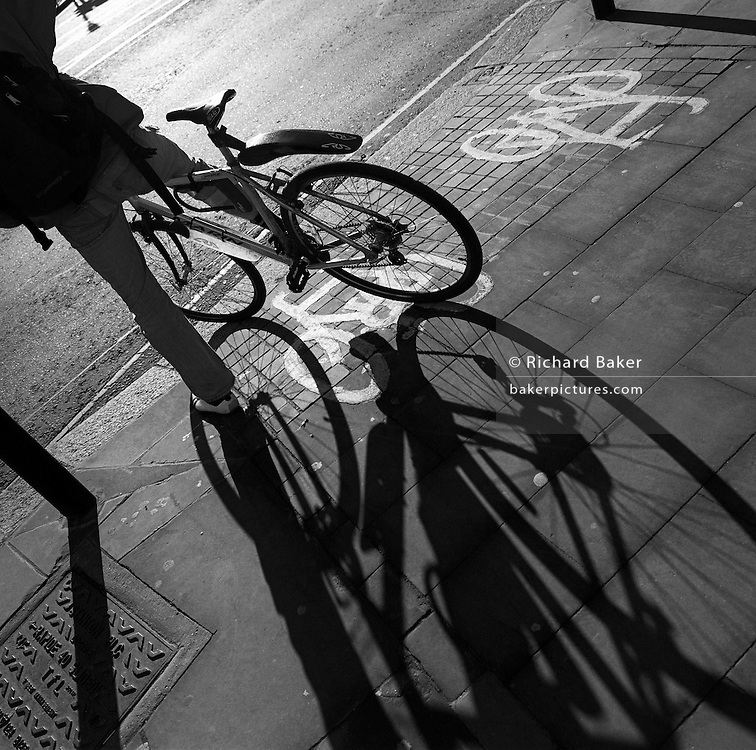 Shadows of a bicycle's wheels and its rider spread across a London pavement (sidewalk).