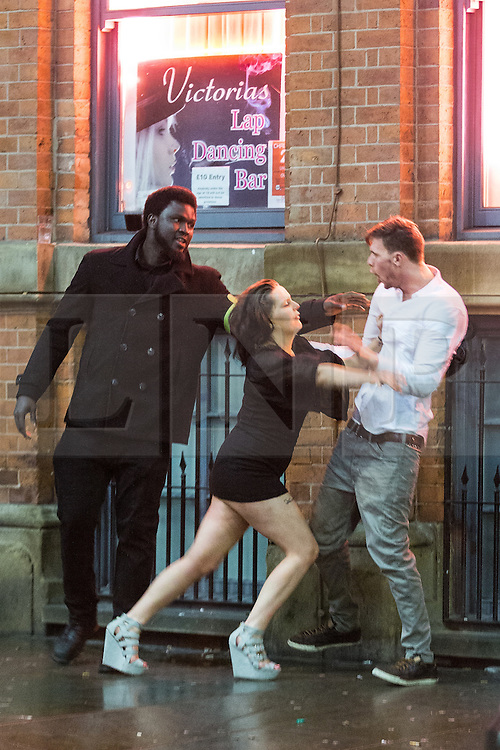© Licensed to London News Pictures . 01/01/2015 . Manchester , UK . A woman pushes a man away from a bouncer outside Victoria's Lap Dancing Bar on Dantzic Street . Revellers usher in the New Year on a night out in Manchester City Centre .  Photo credit : Joel Goodman/LNP