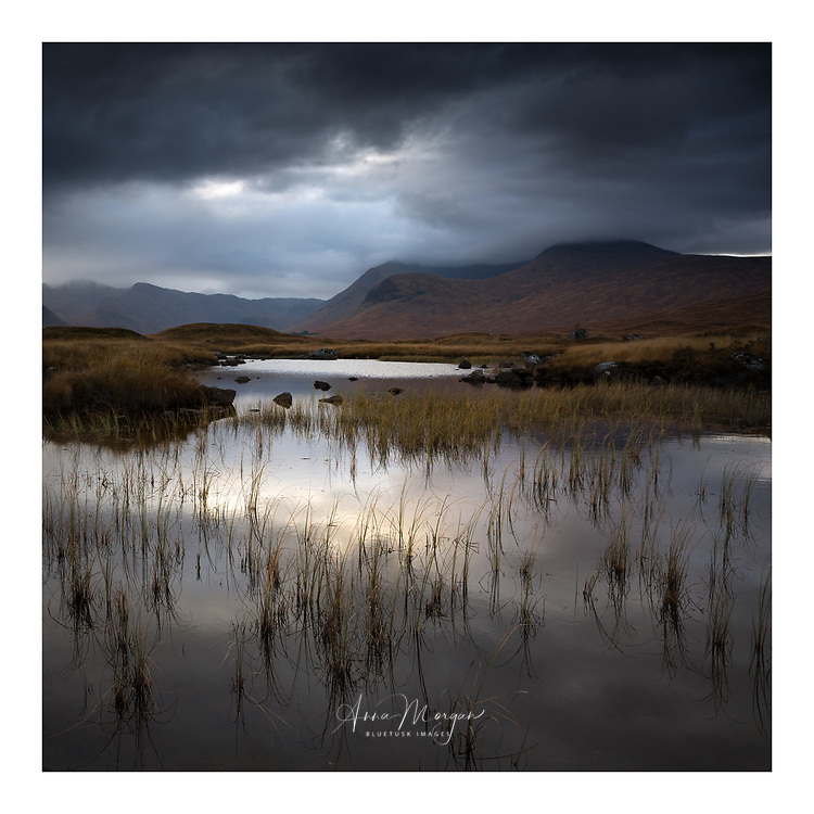 Early Autumn near Glencoe, Scotland. A moody sky is reflected in a still lake surrounded by bog and mountain