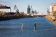 man and woman on slacklines in the Rhine harbor in the district Deutz, in the background the cathedral and Severins bridge, Cologne, Germany.<br /> <br /> Mann  und Frau auf Slacklines im Deutzer Hafen am Rhein, im Hintergrund der Dom und Severinsbruecke, Koeln, Deutschland.