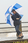 A tourist tries to fight the wind and rain with an umbrella on  the historic Battery as Hurricane Joaquin brings heavy rain, flooding and strong winds as it passes offshore October 3, 2015 in Charleston, South Carolina.