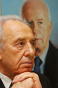 Shimon peres with a painting of Rabin behind him 2.2.04