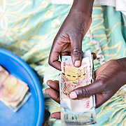 CAPTION: The lessons Florence has learnt have helped her at the women's group that she's a member of. During meetings, she is now able to count the money that the the women have collected. LOCATION: Apapai Parish, Otuboi Sub-county, Kalaki County, Kaberamaido District, Uganda. INDIVIDUAL(S) PHOTOGRAPHED: Florence Agabo.