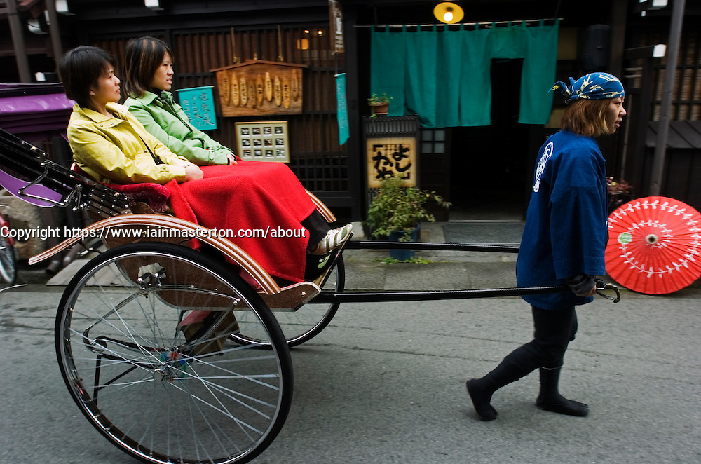 Tourists in rickshaw on guided tour of historic town of Takayama in Japan