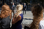 Young women endure strong wind blowing their hair everywhere on the street corner of Fenchurch Street in the City of London, (aka The Square Mile) the capital's financial district, on 3rd September 2019, in London, England.