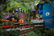 David Reynolds (aka Eco) is a long-term activist, campaigner in the peace movement and resident of the Faslane Peace Camp, Scotland. His home of three years is called the Earth Shack and is largely re-cycled from scrap and garbage found locally on rubbish tips. Eco leans against his garden fence holding a mug of coffee this chilly Sunday morning. Signs of his political beliefs adorn the place: CND logos and Peace on Earth statements. His mother was a 'Carnie' (after the word Carnival, someone working on the fairgrounds) so perhaps it's from her that he more enjoys an alternative outdoor camping lifestyle after a few years in the army. Faslane Peace Camp is a makeshift site alongside Faslane Naval base where Trident nuclear deterrent missiles and submarines dock. The camp has been occupied continuously, in a few different locations, since 1982.