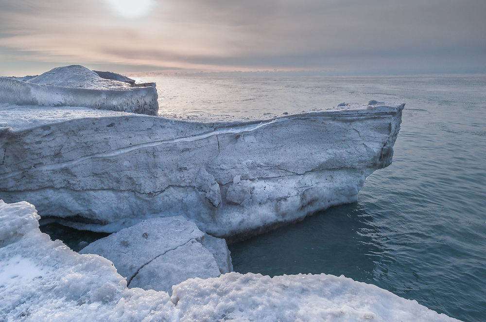 Although I have never had the pleasure of travelling to the Arctic, I felt like I had a small taste of what that environment was like during the winter of 2014 on Lake Ontario. The winter of 2014 was extremely cold and lead to the Great Lake's freezing to a higher degree than most years. Lake Ontario, which usually does not freeze to a high percentage, did freeze quite heavily this year. This provided many opportunities for photography, and I found myself making many visits to the shoreline, either in early morning or later in the day. In this photo I walked, with cleats to the edge of the shoreline ice and photographed the structure of the thick ice along the shoreline. The rising sun provided a cool blue, orange light that highlighted the ice, water and sky.